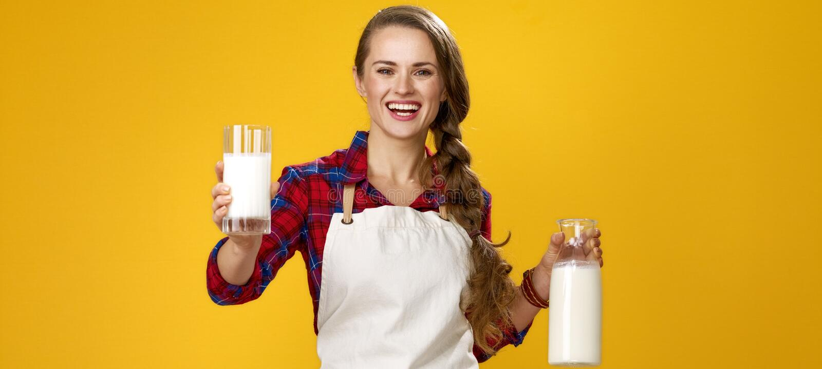 Smiling woman cook giving glass of homemade fresh raw milk royalty free stock image