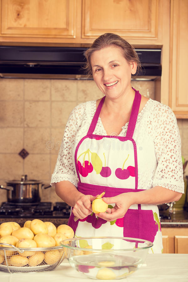 Smiling woman cooking in her kitchen royalty free stock images