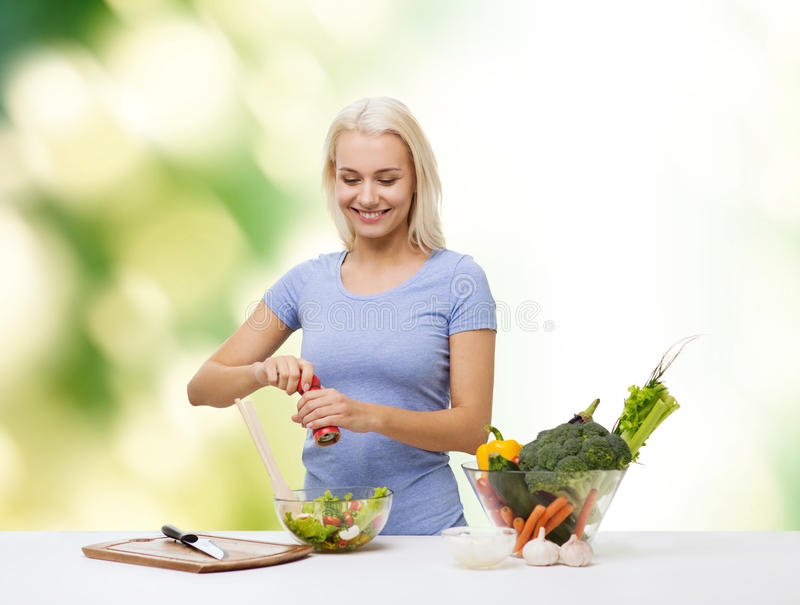 Smiling woman cooking vegetable salad stock photography