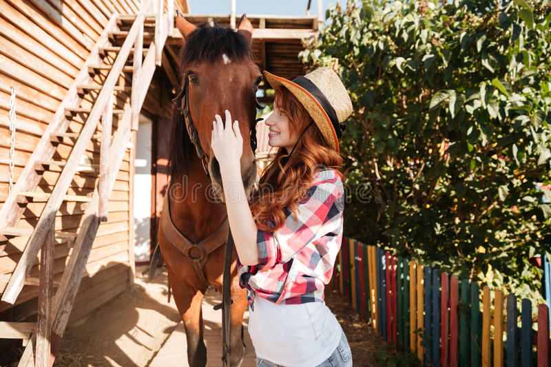 Smiling woman cowgirl taking care of her horse on farm stock photography