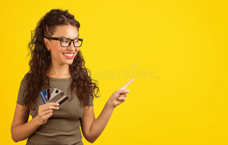 Smiling woman with credit cards pointing away royalty free stock image