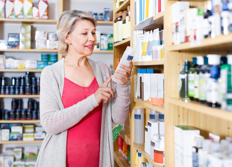 Smiling woman customer browsing rows of skin care products royalty free stock image