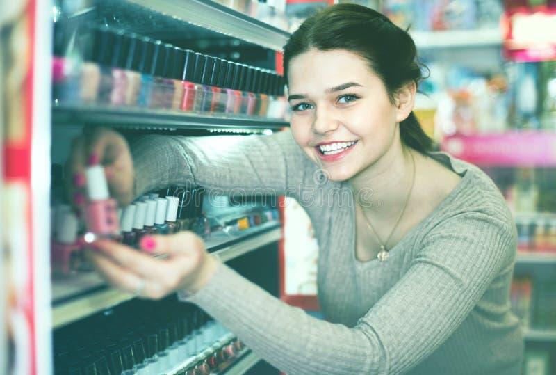 Smiling woman customer deciding on nail polish stock photography