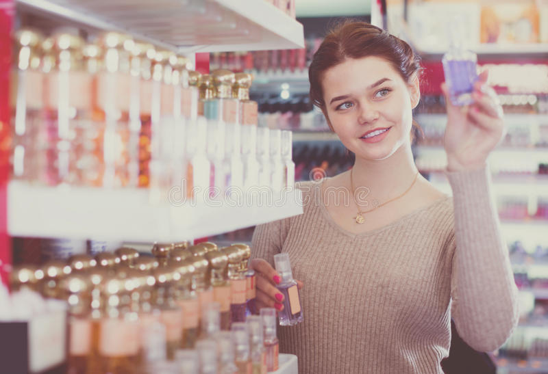 Smiling woman customer deciding on perfume variants in cosmetics royalty free stock photography