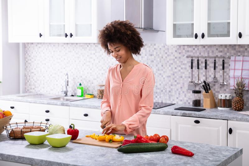 Smiling Woman Cutting Vegetables On Chopping Board royalty free stock photos