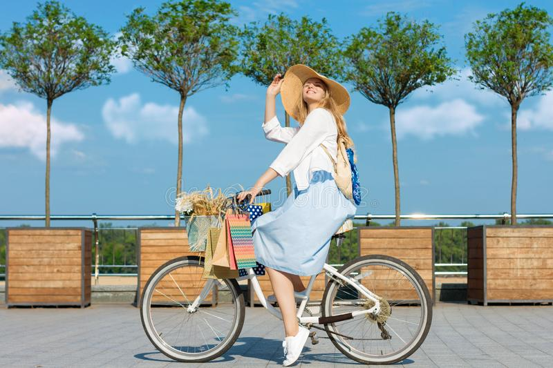 Woman is cycling in blue dress on white bicycle with basket of flowers royalty free stock photos