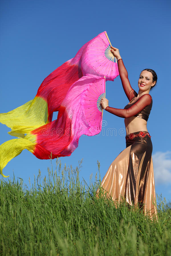 Smiling woman dances with veil fans royalty free stock photo