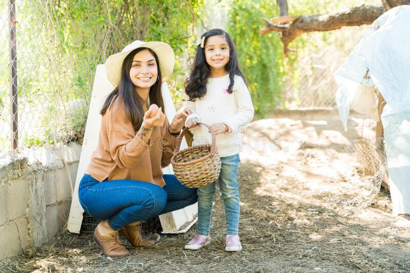 Smiling Woman And Daughter With Egg At Farm stock photo