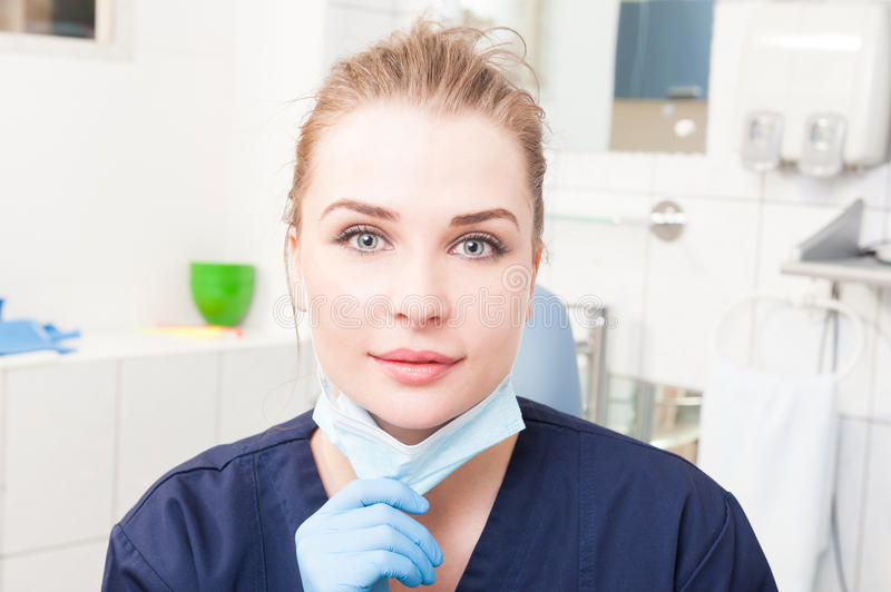 Smiling woman dentist in close-up holding dental mask royalty free stock images