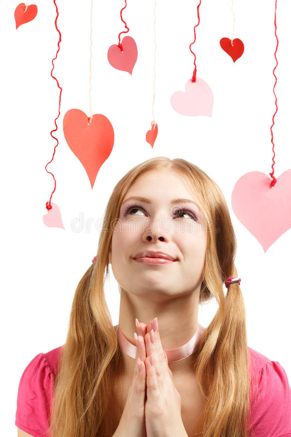 Smiling woman with designer red and pink paper valentine hearts. Beautiful young smiling woman with designer red and pink paper valentine hearts hanging on royalty free stock photography