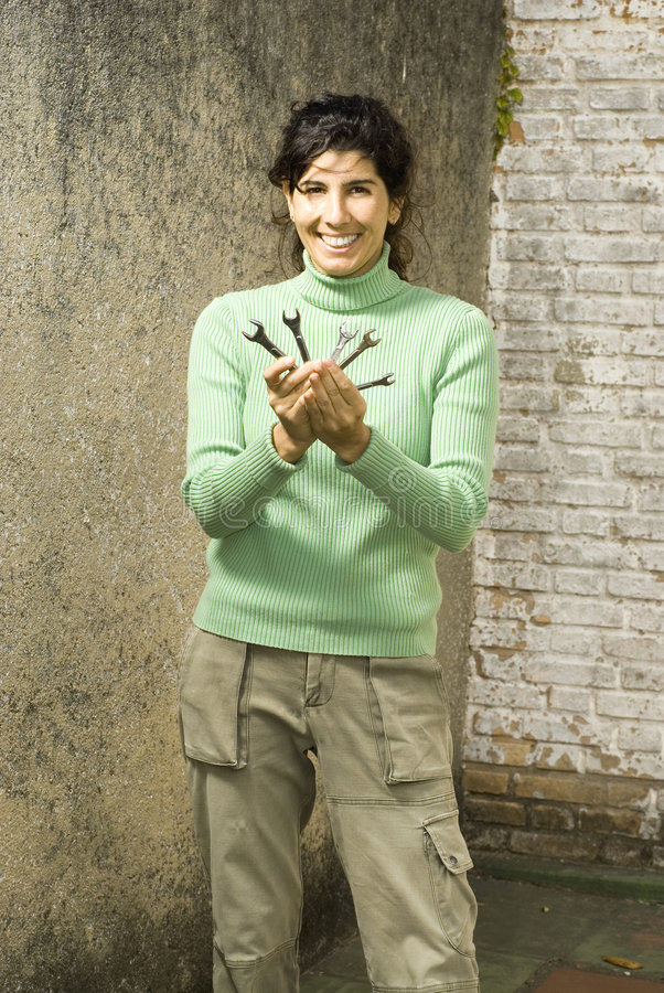 Smiling Woman Displays Wrenches royalty free stock photos