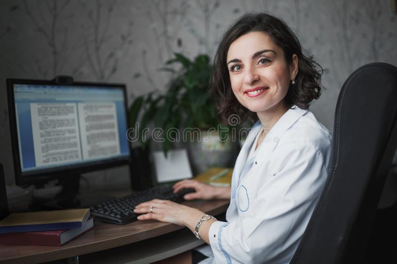 Smiling woman doctor in a white medical robe sitting at a table. On the table books, a computer monitor and a green plant. The hor royalty free stock images