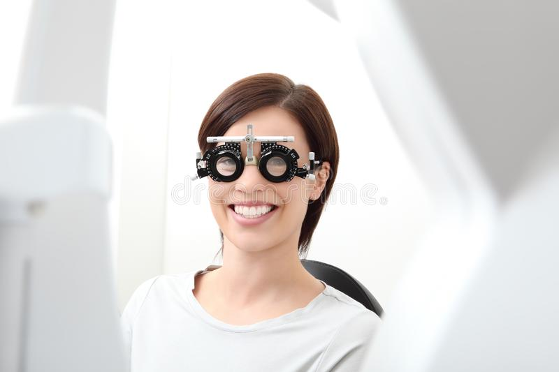 Smiling woman doing eyesight measurement wears trial frame isolated on white. Smiling woman doing eyesight measurement wears trial frame on white royalty free stock image