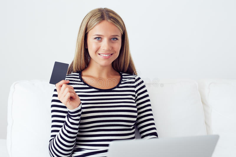 Smiling woman doing online shopping with laptop royalty free stock images