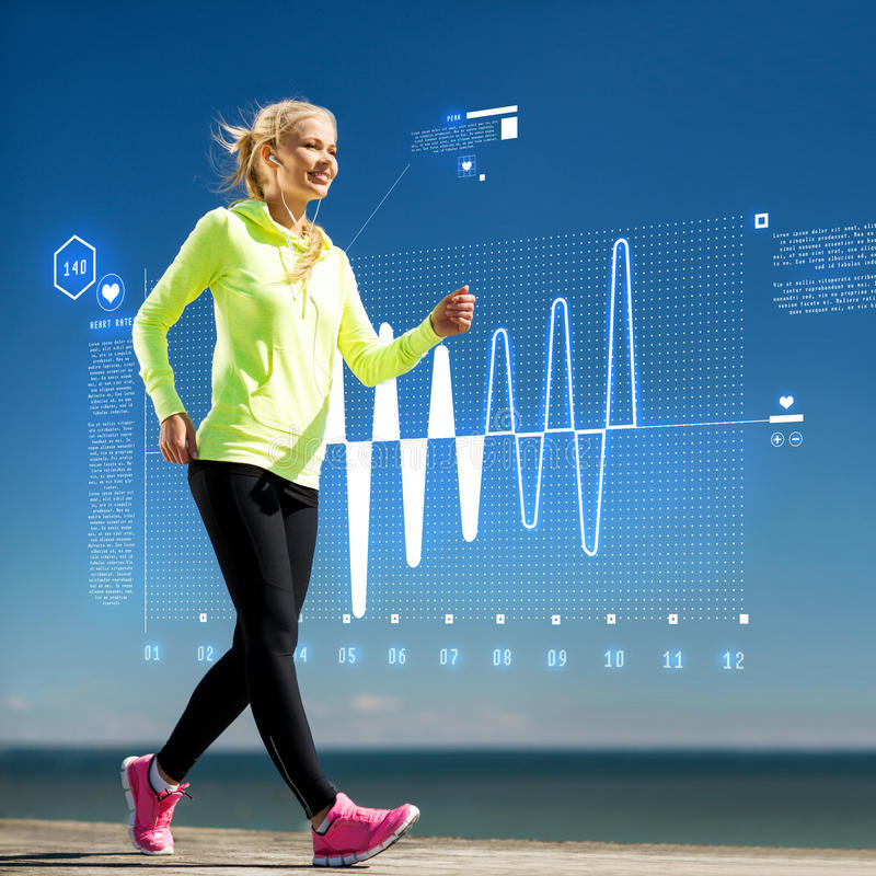 Smiling woman doing sports outdoors with earphones royalty free stock image