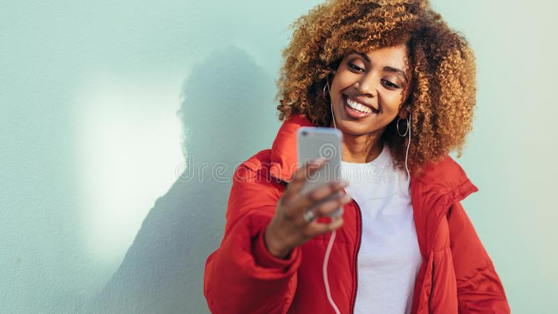 Smiling woman doing a video chat on mobile phone stock photos