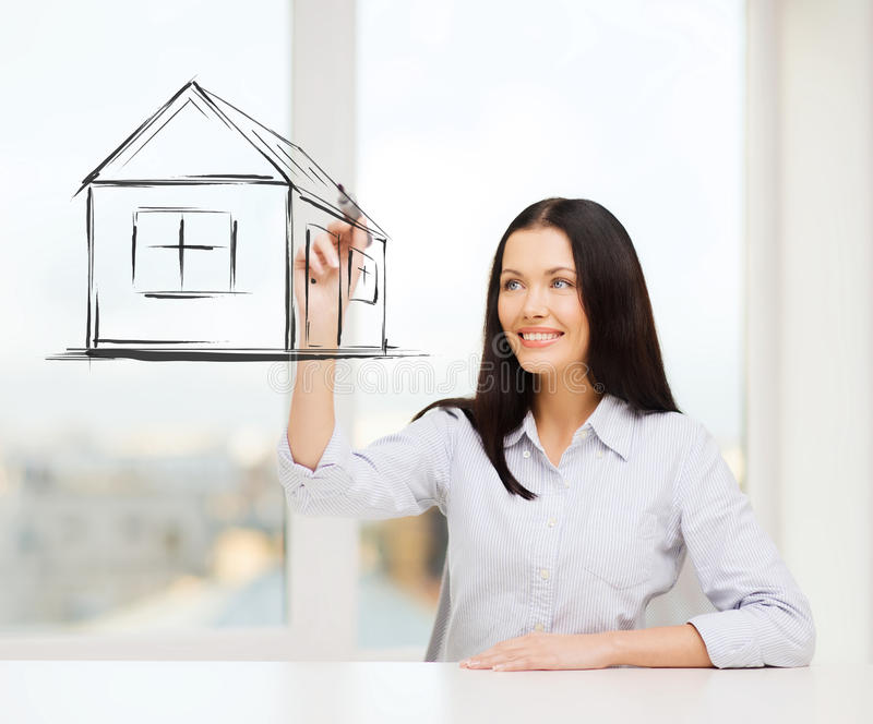 Smiling woman drawing house on virtual screen. Real estate, accomodation and technology concept - smiling woman drawing house on virtual screen stock photo