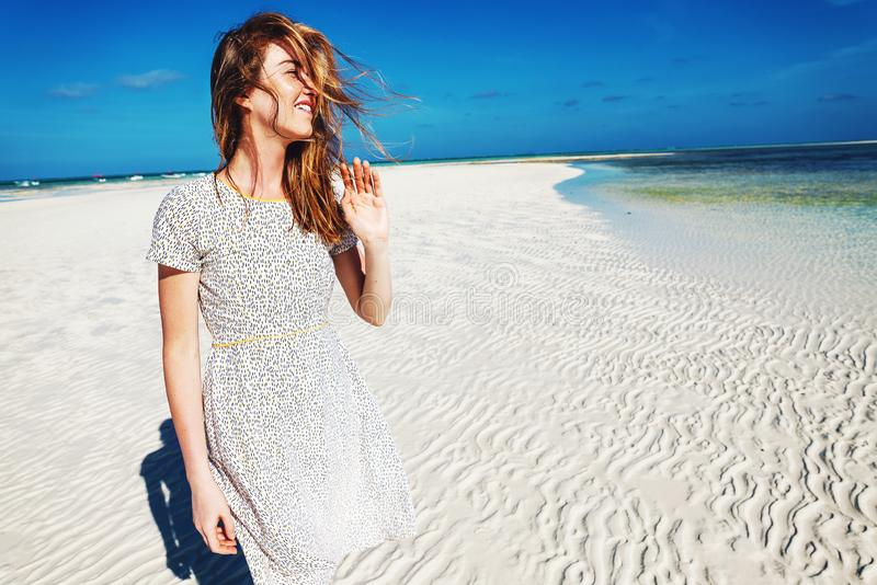 Smiling woman in dress on white sand beach stock images