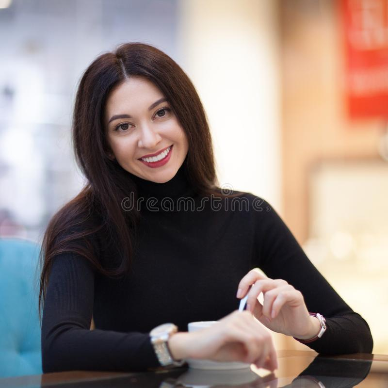 Smiling woman drinking coffee in cafe. Portrait of beautiful happy stylish woman. Fashion lifestyle. Woman style, trendy outfit royalty free stock photography