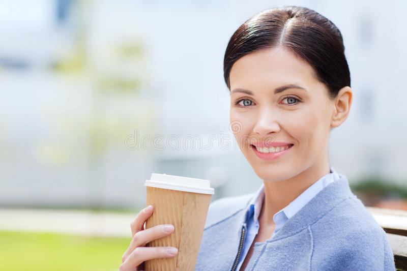 Smiling woman drinking coffee outdoors. Drinks, leisure and people concept - smiling woman drinking coffee outdoors stock photo