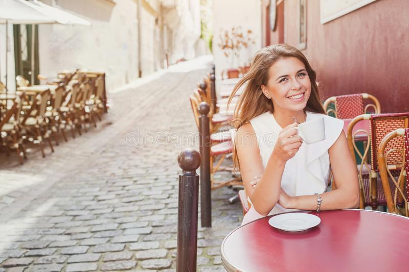 Smiling woman drinking coffee in street cafe royalty free stock photography