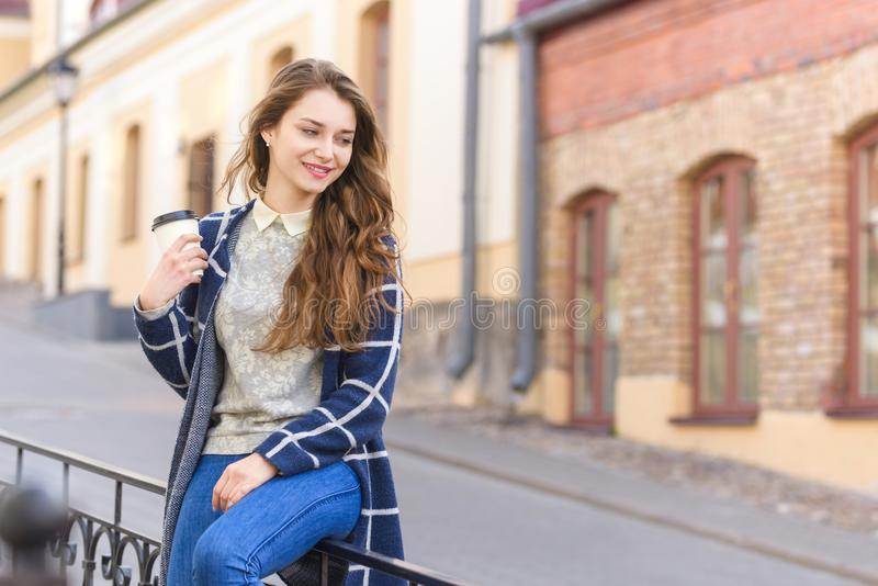 Smiling woman drinking coffee in street stock photo