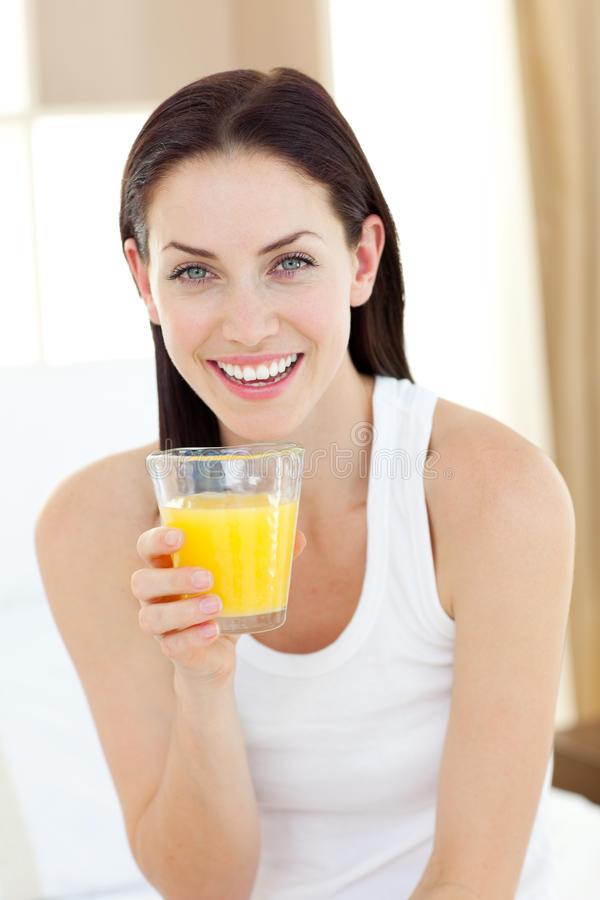 Smiling woman drinking orange juice stock image