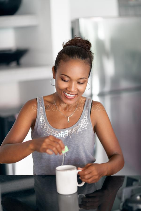 Smiling woman drinking tea in kitchen stock image