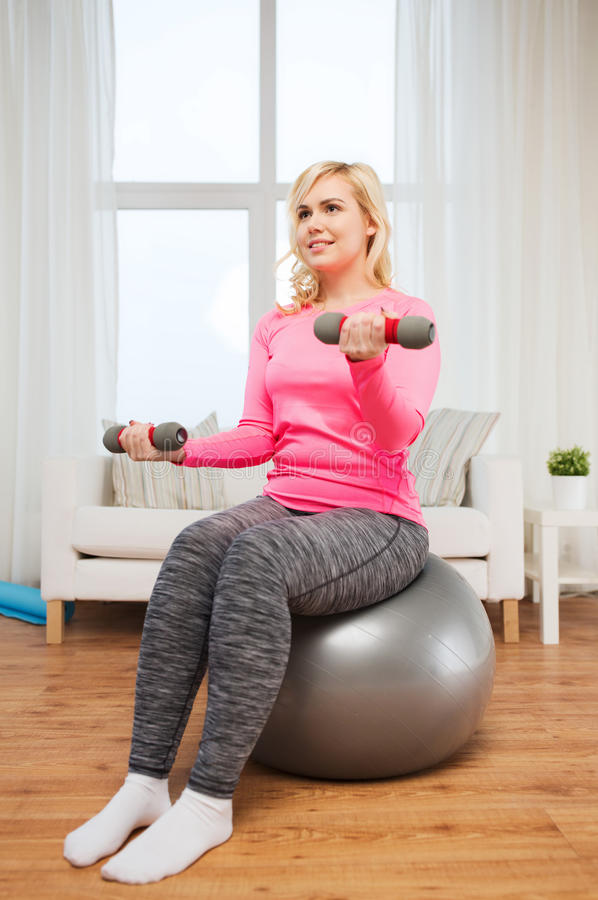 Smiling woman with dumbbells exercising at home. Fitness, sport, training and lifestyle concept - smiling woman with dumbbells and fit ball exercising at home royalty free stock photo