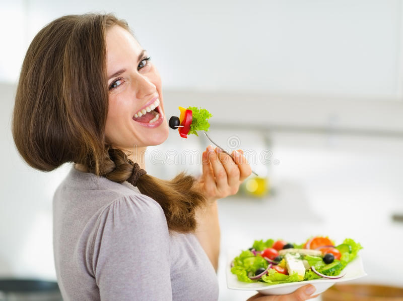 Smiling woman eating fresh salad in kitchen stock photos