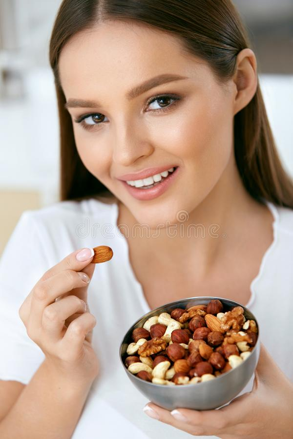 Smiling Woman Eating Nuts In Kitchen. Portrait Of Beautiful Happy Woman Holding Nut Bowl, Eating Healthy Food For Breakfast. Nutrition And Diet. High Quality royalty free stock photo