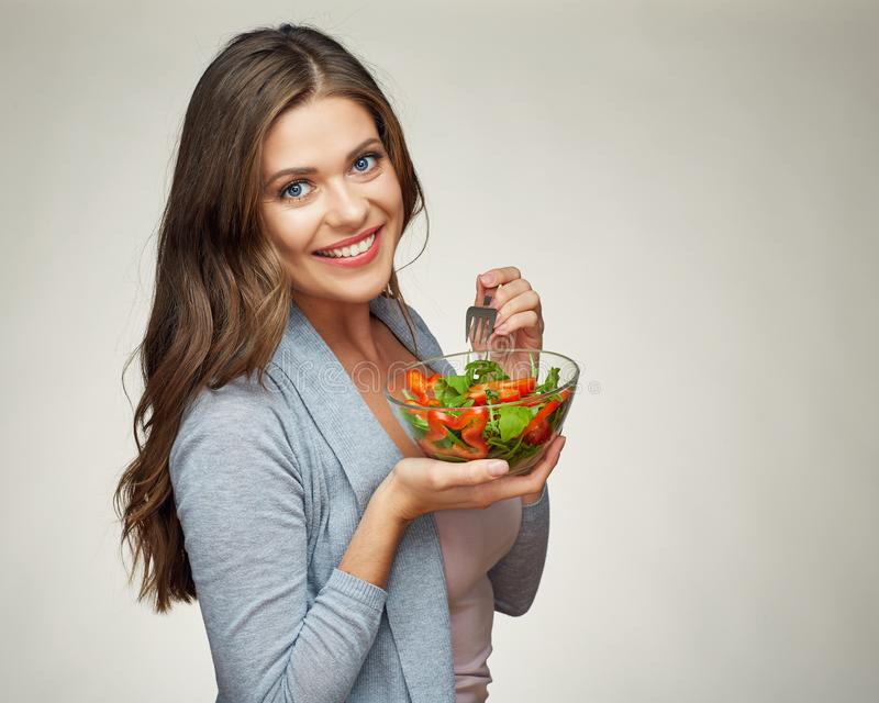 Smiling woman eating salad. portrait of beautiful girl royalty free stock image