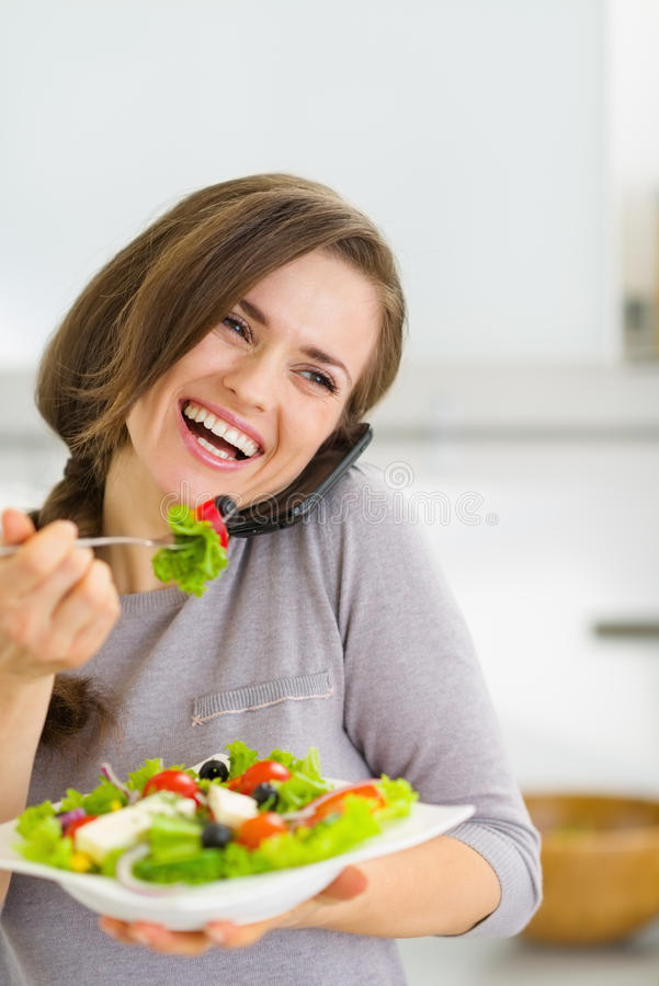 Smiling Woman Eating Salad And Talking Mobile Phone Stock Images