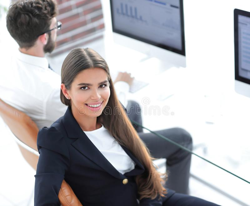 Smiling woman employee sitting at a Desk. Smiling women employee sitting at a Desk and looking at camera.photo with copy space royalty free stock photos