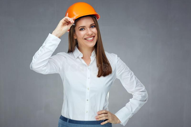 Smiling woman engineer builder worker touching her protect helmet. Gray wall back isolated stock image