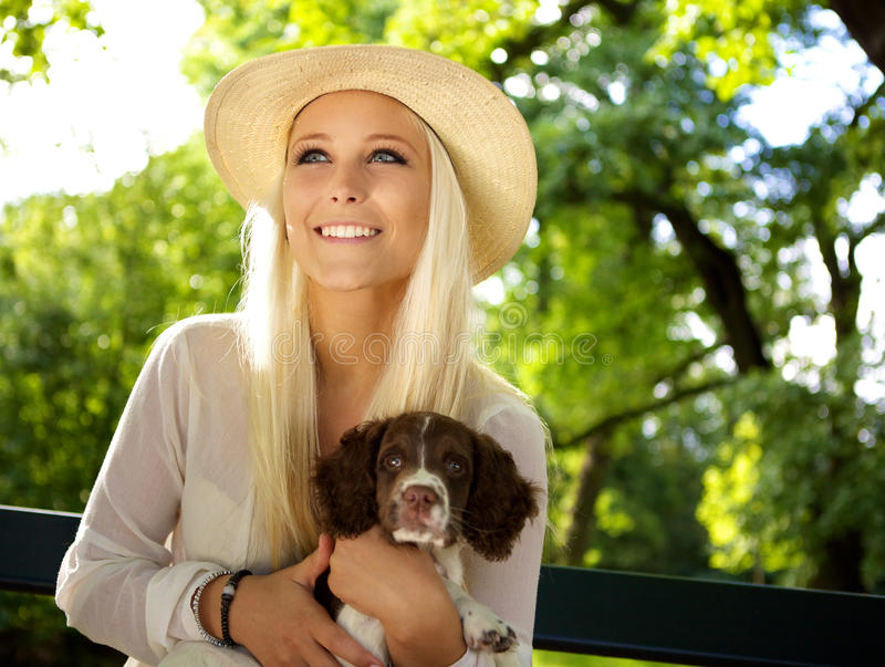 Smiling woman with a English Springer Spaniel. Cute woman holding a English Springer Spaniel puppy in her arms on a park bench stock image