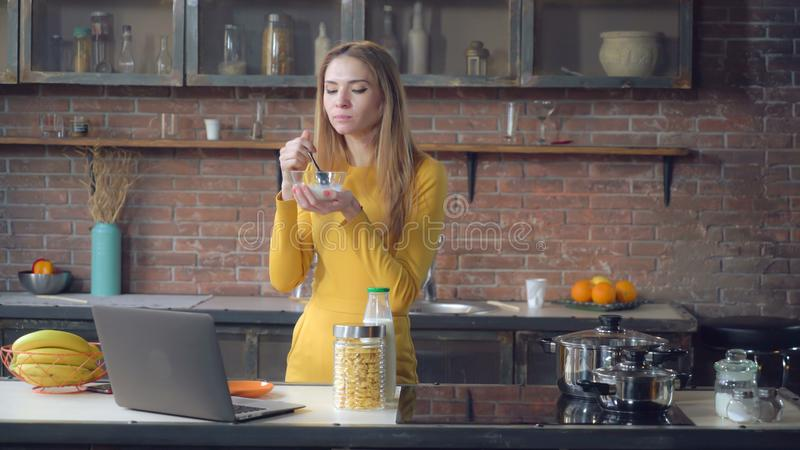 Lady eating in loft apartment with happy smile. Smiling woman enjoy breakfast in the kitchen. Caucasian businesswoman relish cereal with milk in the morning at stock images