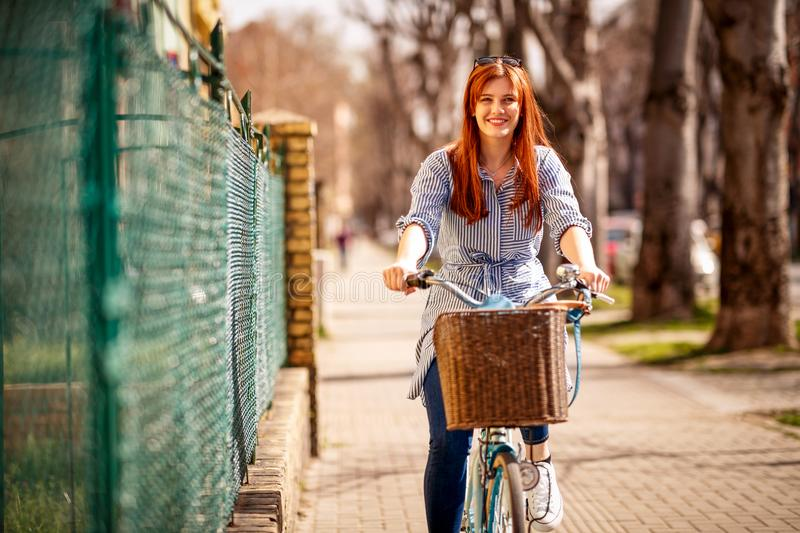 Smiling woman enjoying on a bike during day in city stock images