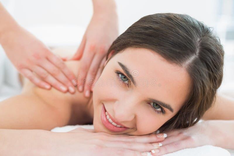 Smiling woman enjoying shoulder massage at beauty spa stock photo