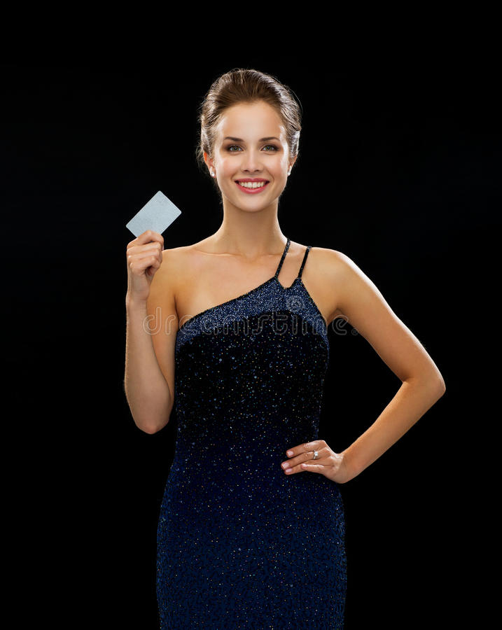 Smiling woman in evening dress holding credit card. Wealth, money, luxury and people concept - smiling woman in evening dress holding credit card over black royalty free stock image