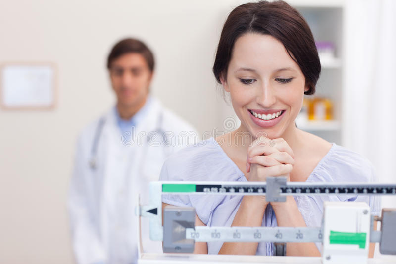 Smiling woman excited about the scale stock photos