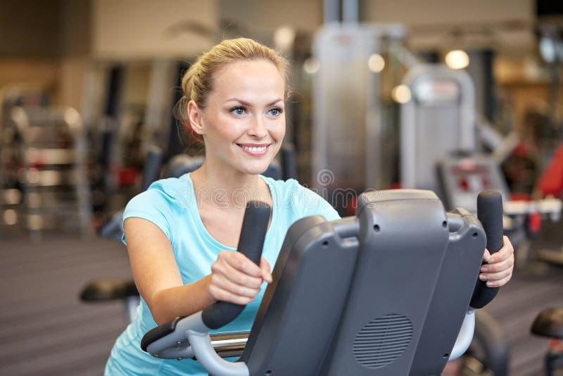 Smiling woman exercising on exercise bike in gym royalty free stock photos