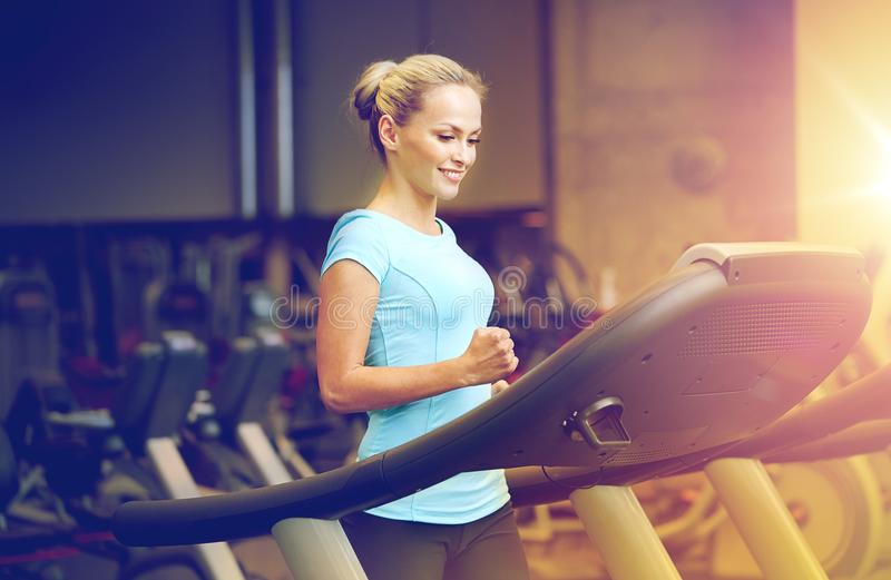 Smiling woman exercising on treadmill in gym stock images