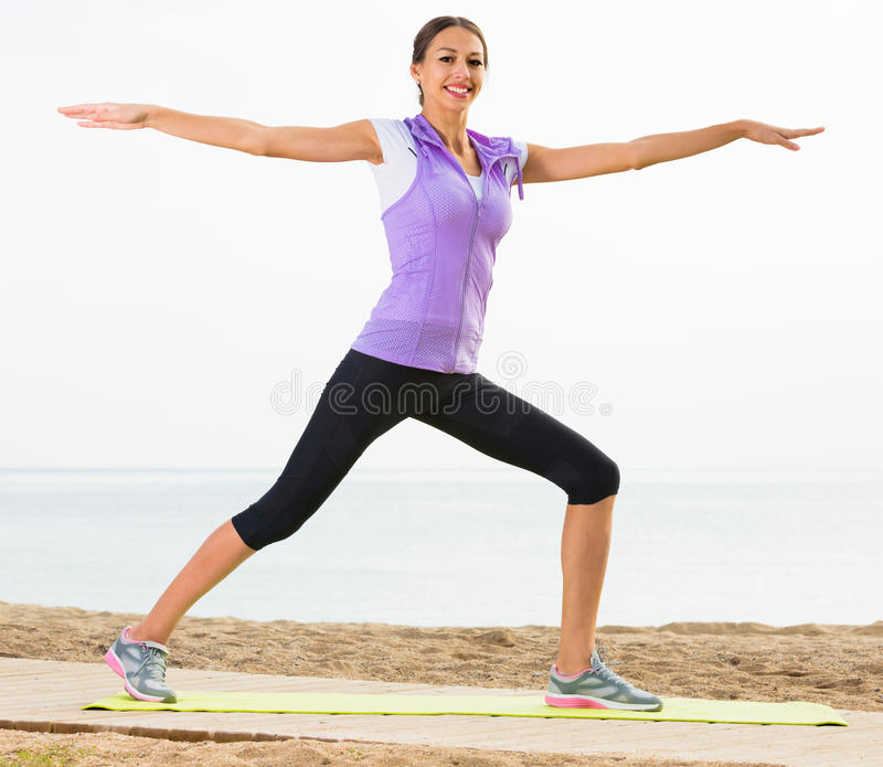 Download Smiling Woman Exercising Yoga Poses On Beach Stock Image - Image of balance, smiling: 83701567