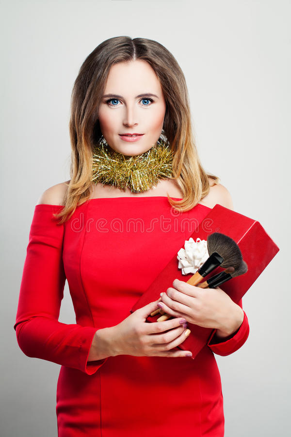 Smiling Woman Fashion Model in Red Dress with Christmas Gift Box stock image