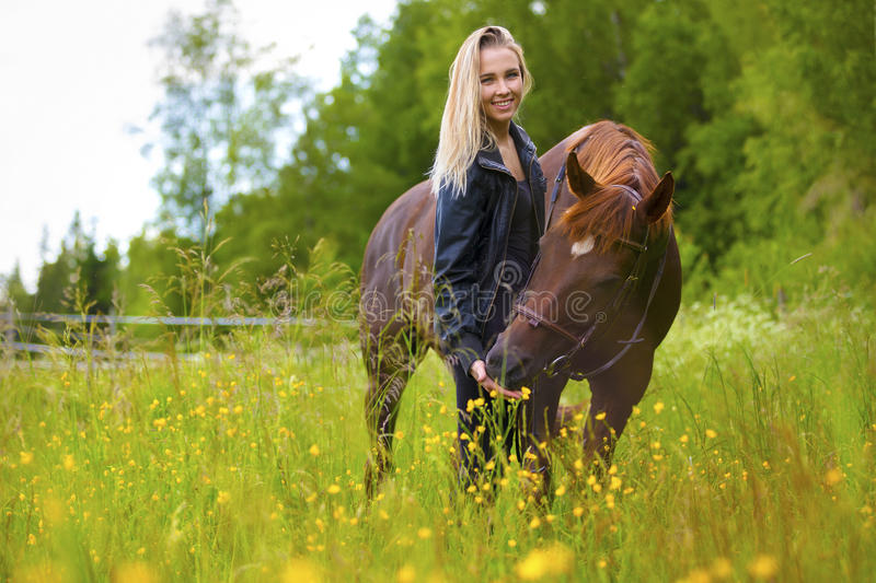 Smiling woman feeding her arabian horse with snacks in the field stock photos