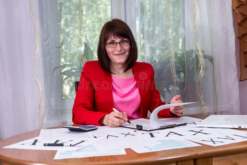 Smiling woman filling 1040 tax form in office.  stock photo