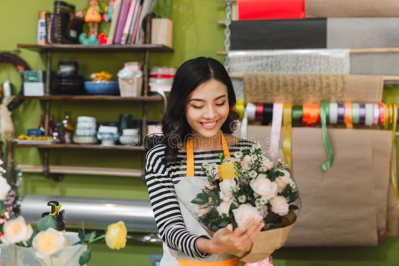 Smiling woman florist, small business flower shop owner, at counter, looking friendly at camera working at a special flower. Arrangement royalty free stock image