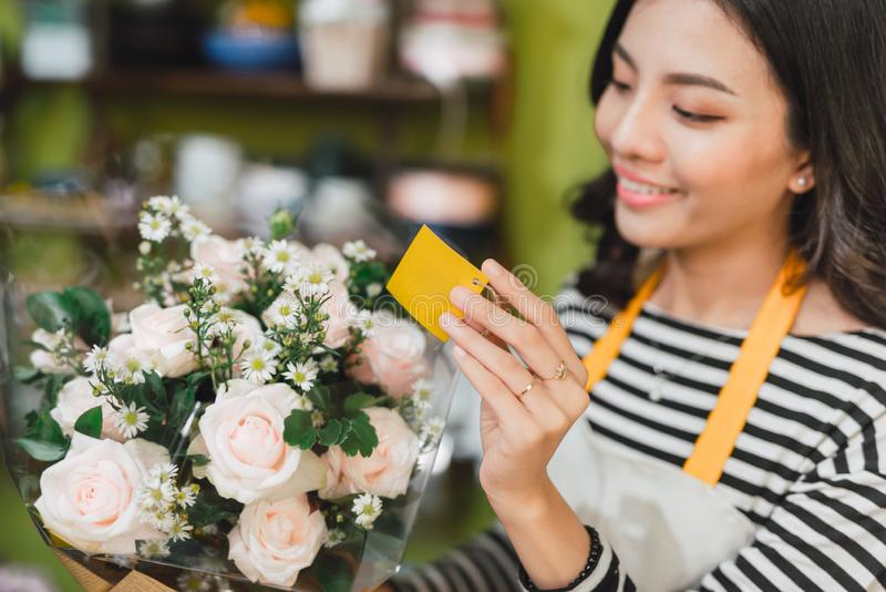 Smiling woman florist, small business flower shop owner, at counter, looking friendly at camera working at a special flower stock photography