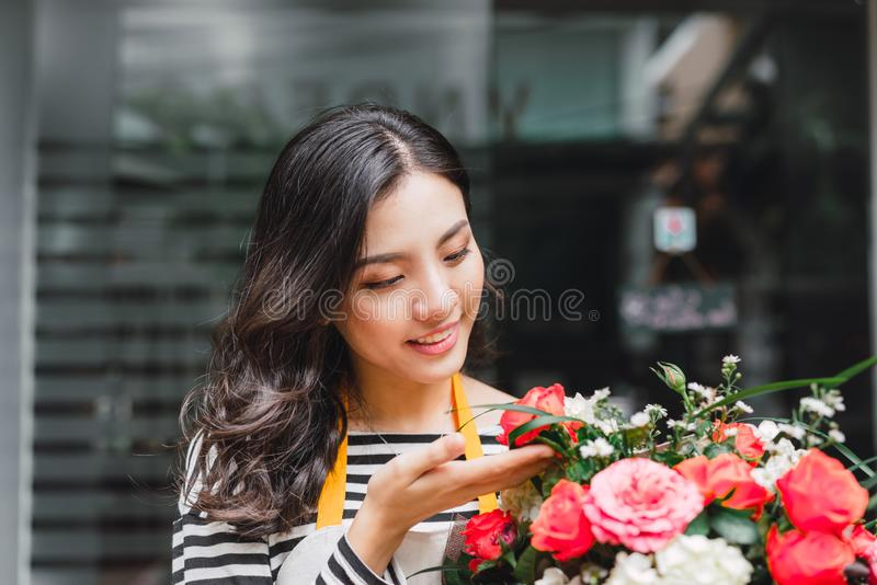 Smiling woman florist, small business flower shop owner, at counter, looking friendly at camera working at a special flower royalty free stock photos